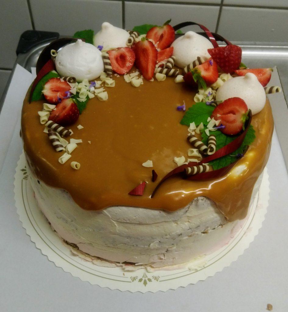 Kinuskidripillä koristeltu marenkivoikreemillä kuorrutettu kakku.